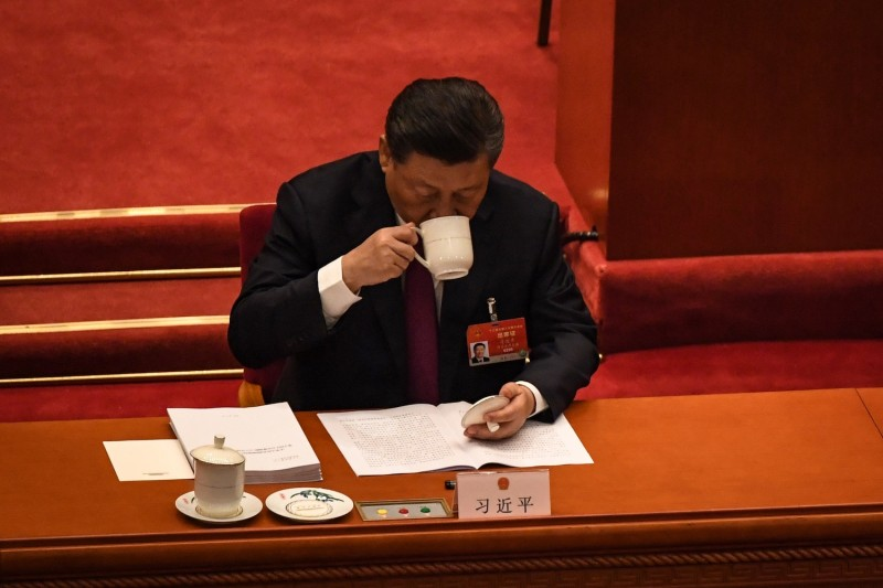 China's President Xi Jinping drinks tea as he reads a work report during the opening session of the National People's Congress (NPC) at the Great Hall of the People in Beijing on March 5, 2021. (Photo by Leo RAMIREZ / AFP) (Photo by LEO RAMIREZ/AFP via Getty Images)