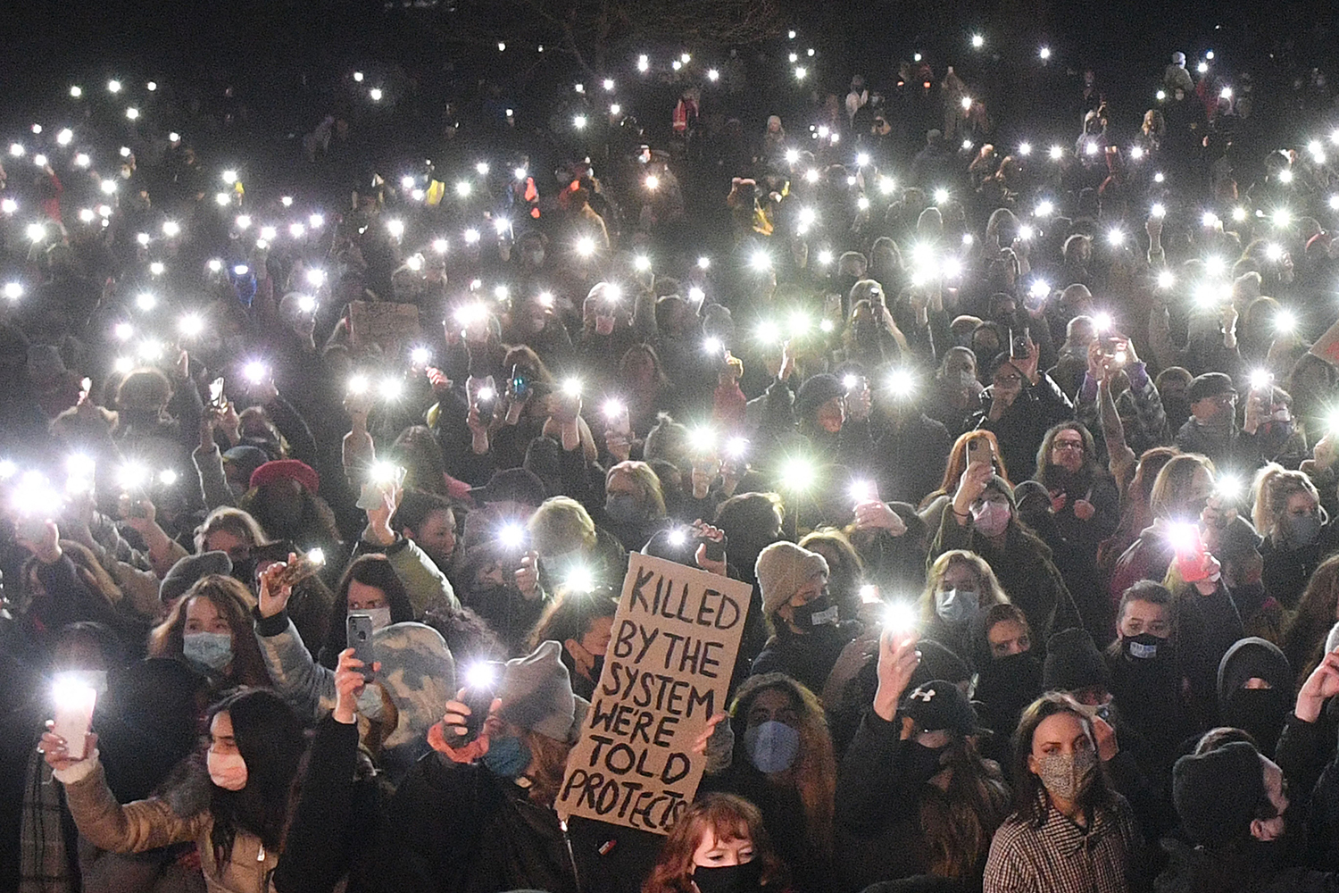 People hold up their phone flashlights as they gather at a bandstand in London for a vigil that was planned for Sarah Everard but canceled because of COVID-19 restrictions March 13. The police officer charged with killing Everard, who disappeared while walking home from a friend's house, appeared in court earlier that day. JUSTIN TALLIS/AFP via Getty Images