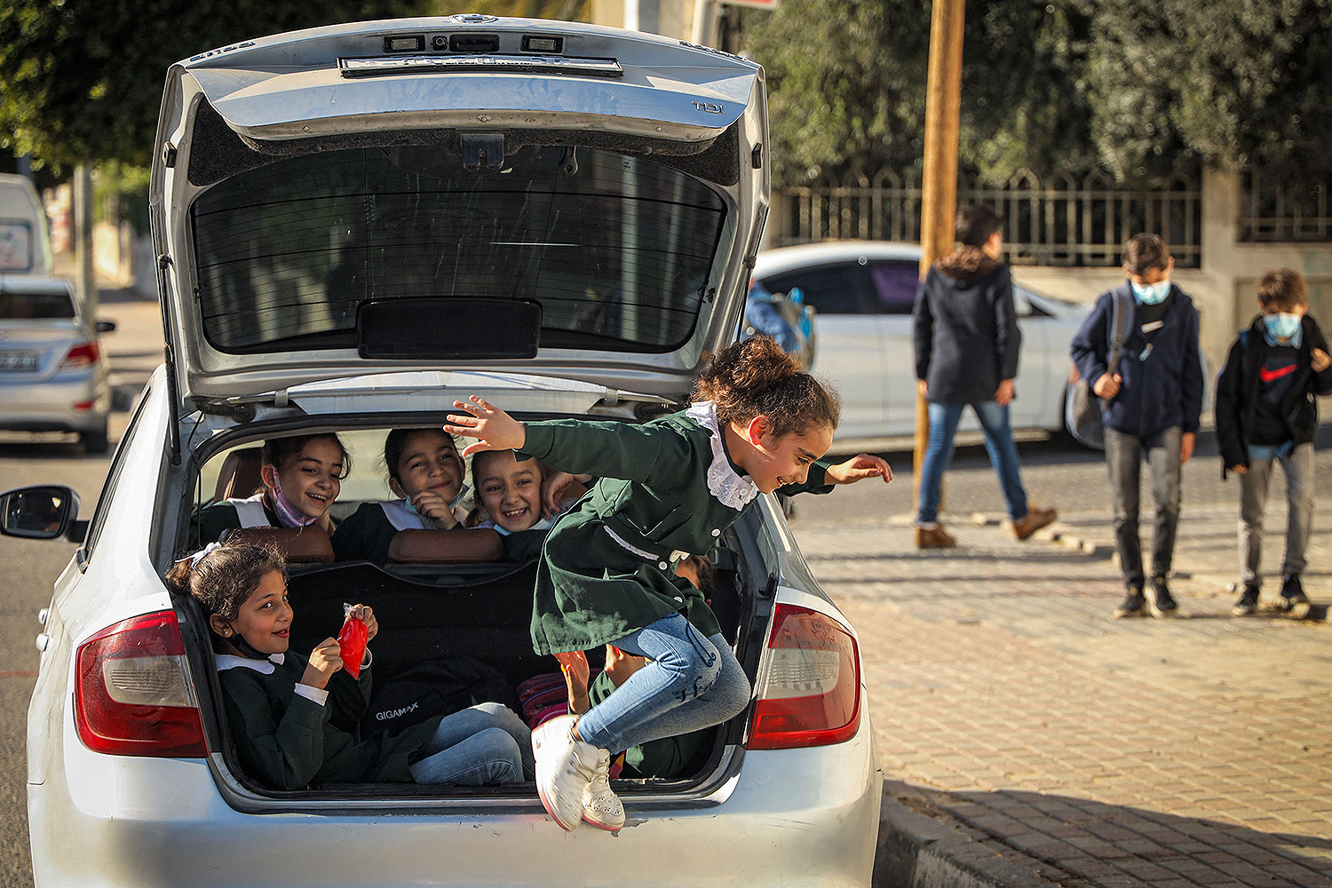 A schoolgirl leaps from the trunk of a car after leaving school in Gaza City on March 17. MOHAMMED ABED/AFP via Getty Images