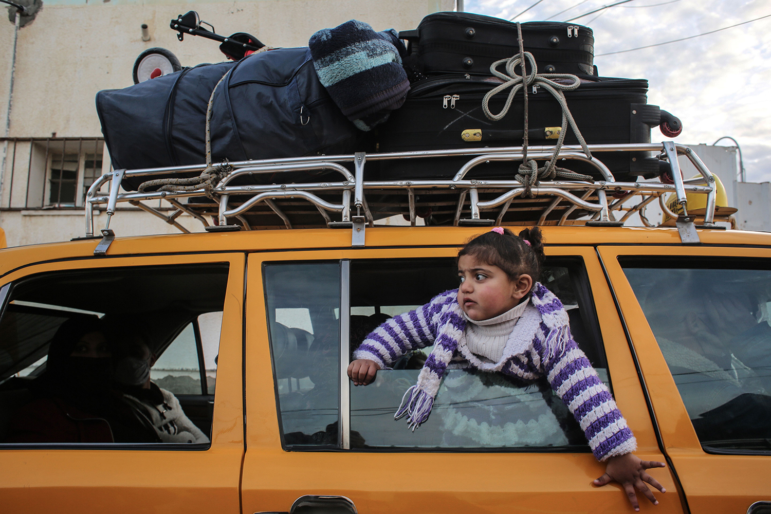 A girl looks out the window of a vehicle loaded with suitcases as it waits at the Rafah border crossing to travel from the Gaza Strip into Egypt on Feb. 9. SAID KHATIB/AFP via Getty Images