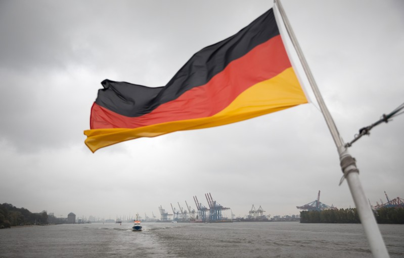 A German flag flutters at the stern of an excursion ship over the container gantry cranes of the Port of Hamburg on Oct. 26, 2018.