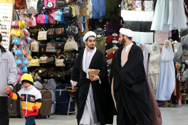 Clerics walk along a market street near the Fatima Masumeh shrine in Iran's holy city of Qom