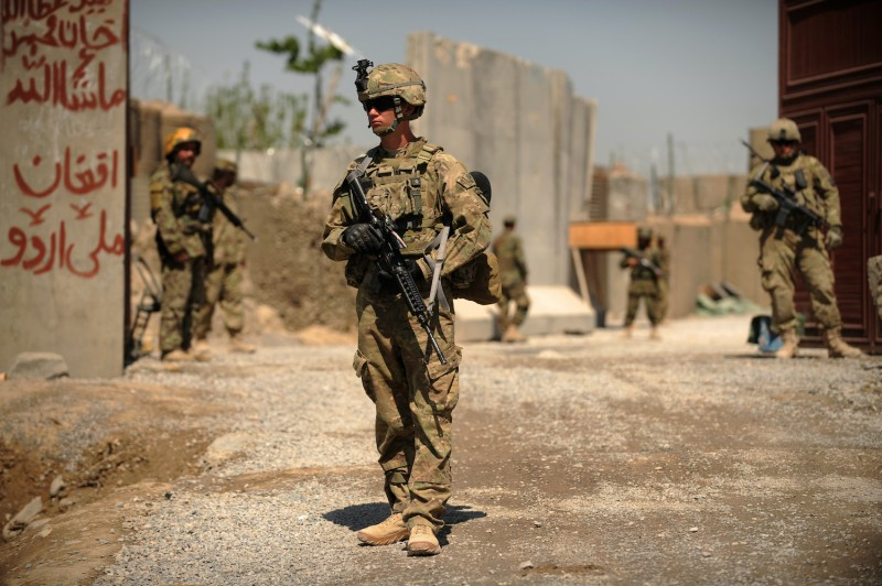 US soldiers from 1st Regiment 320 Field Artillary 101st Airbourne stand guard outside COP Stout before the opening ceremony for a newly completed mosque in the village of Tarok Kolache in southern Kandahar province on April 1, 2011 where the US military is funding its rebuilding.