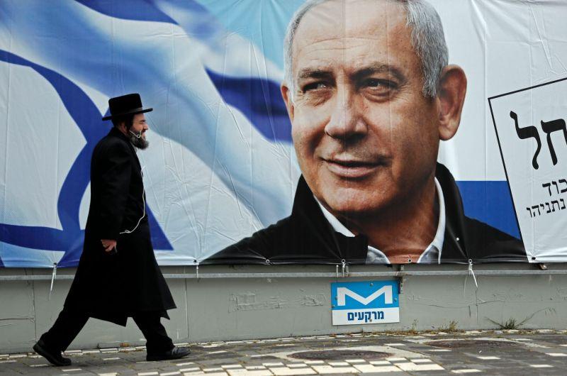 An ultra-Orthodox Jewish man walks past a billboard of Israel's Benjamin Netanyahu.