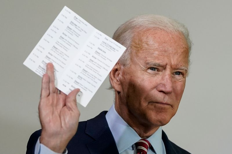 Joe Biden holds up a copy of his daily schedule, which includes statistics about how many U.S. troops have died while serving in Afghanistan and Iraq and updates about the coronavirus caseload in the U.S., while speaking before a roundtable event with military veterans at Hillsborough Community College on Sept. 15, 2020 in Tampa, Florida.