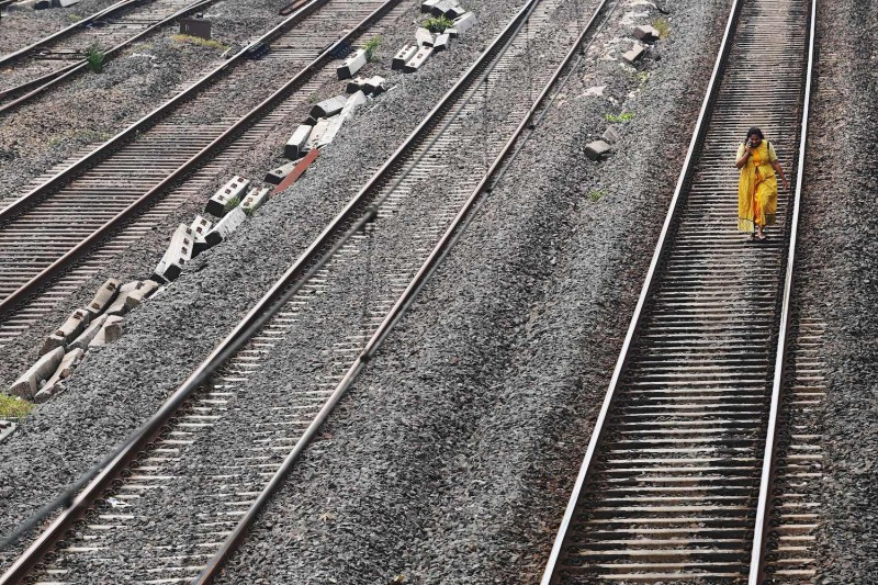 A passenger walks on a railway track after trains got stranded due to a major power outage from grid failure in Mumbai on Oct. 12, 2020.