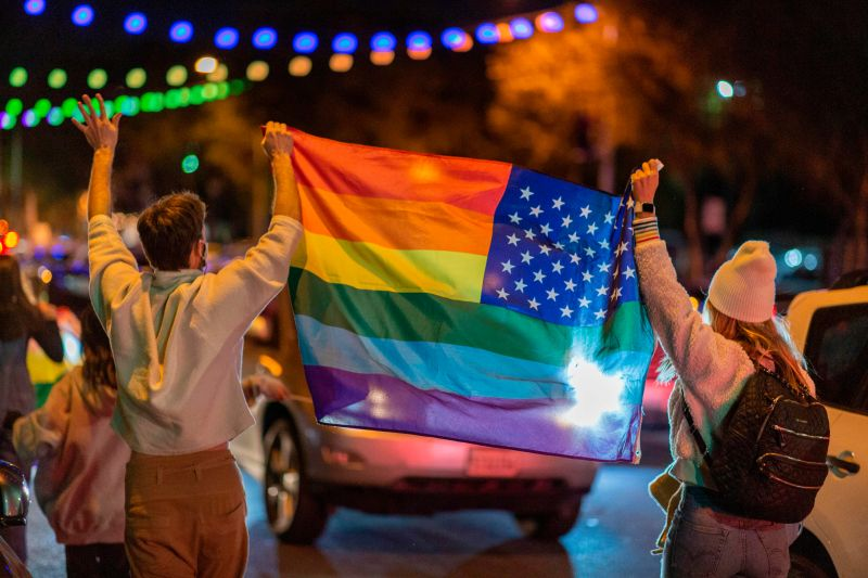 People wave a rainbow flag as they celebrate the victory of Joe Biden in the 2020 presidential election in West Hollywood, California, on Nov. 7, 2020.