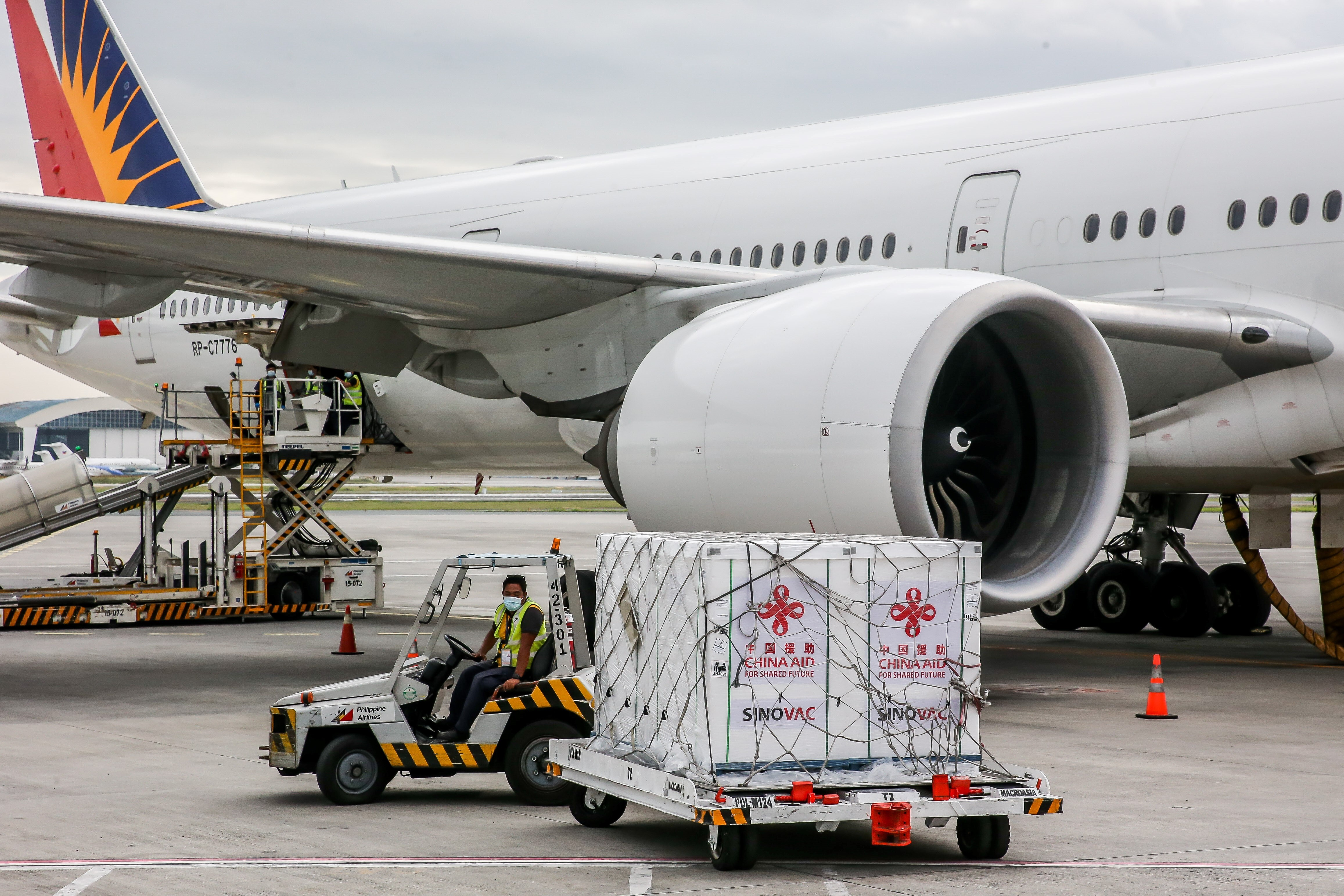 Staff members transport the second batch of the Sinovac vaccine donated by China at the Ninoy Aquino International Airport in Manila on March 24.