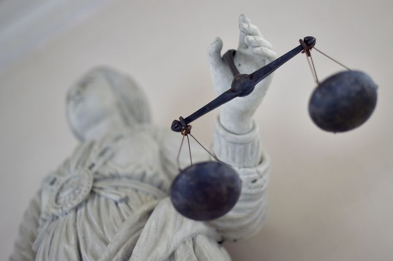 A statue of the goddess of justice sits at a French courthouse.