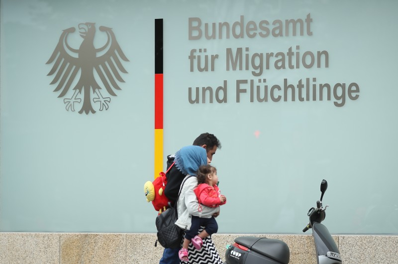 A family walks past the Federal Office for Migration and Refugees.