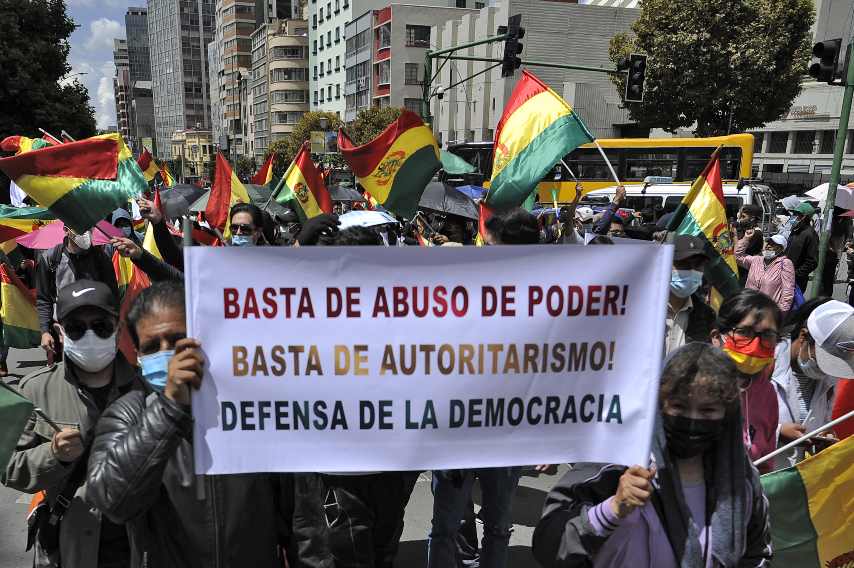 "Opponents of Bolivian President Luis Arce hold a banner that translates to ""enough abuse of power, enough authoritarianism, defend democracy"" during a march to protest the arrest of former interim President Jeanine Anez on March 17."