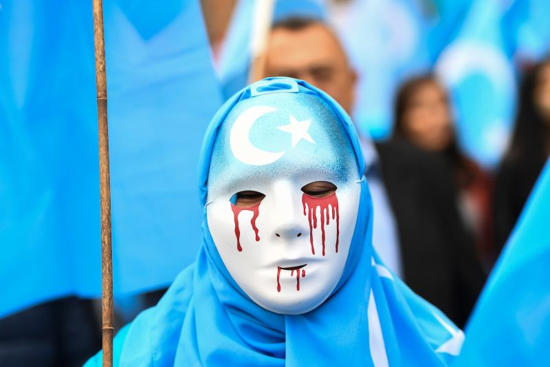 A person wearing a white mask with red tears takes part in a march calling on the European Union to condemn China's treatment of the Uyghur population in Brussels on April 27, 2018.