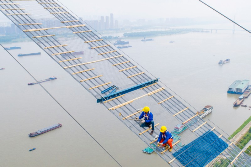 Workers construct a double-decker suspension bridge across the Yangtze River in Wuhan, China on May 8, 2018.