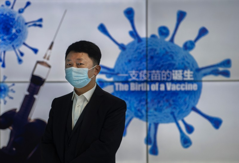 A representative stands in front of a monitor at Sinopharm CNBG's COVID-19 vaccine production facility during a media tour in Beijing on Feb. 26.