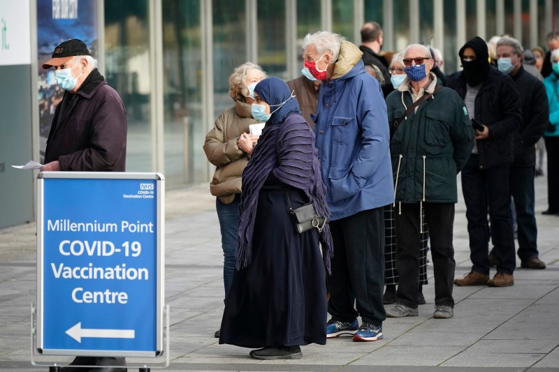People line up outside a mass COVID-19 vaccine center at the Millennium Point center in Birmingham, England, on Jan. 11.