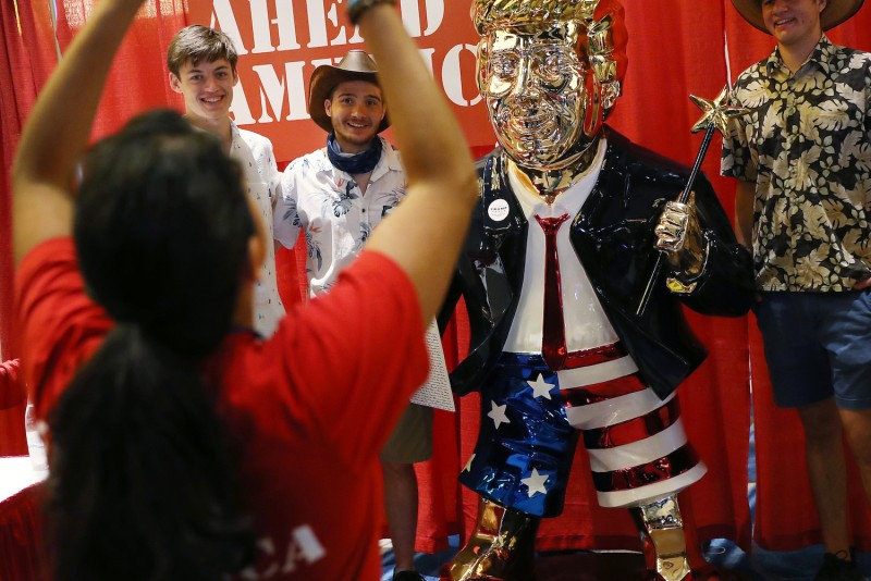 People take a picture with a gold statue of former President Donald Trump at the Conservative Political Action Conference in the Hyatt Regency in Orlando, Florida on Feb. 27.