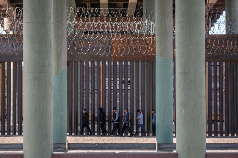 Migrants walk along the U.S.-Mexico border wall in Ciudad Juárez, Mexico, on March 17.