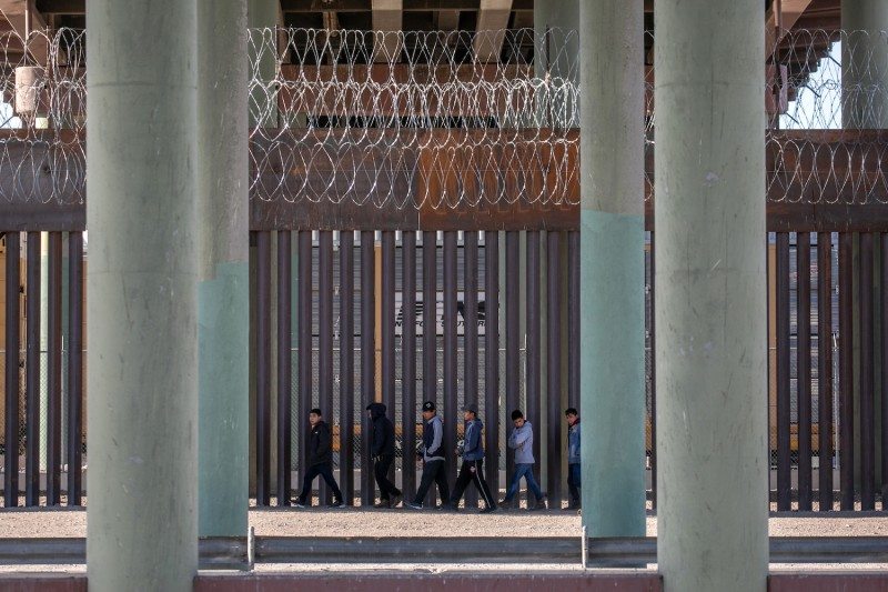 Migrants walk along the U.S.-Mexico border wall in Ciudad Juárez, Mexico, on March 17.