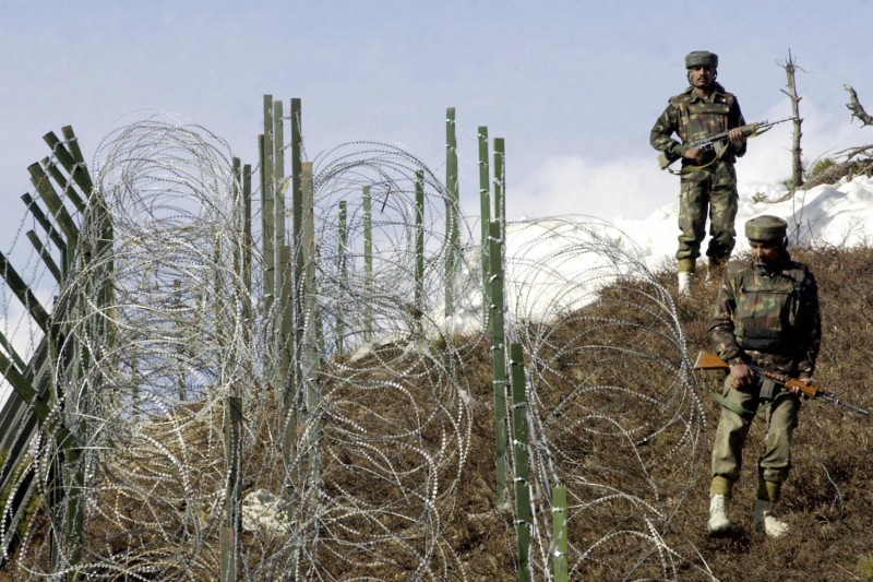 Indian soldiers patrol along a barbed-wire fence near Baras Post on the Line of Control on Dec. 4, 2003.