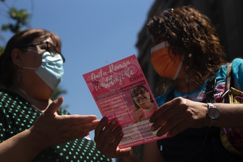 Anita Román, a constituent candidate for the People's List, talks to a woman in downtown Santiago, Chile, on Dec. 30, 2020.