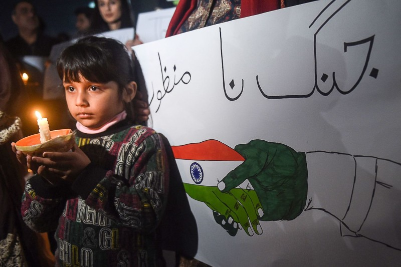 A Pakistani girl holds a candle during a vigil for peace in Lahore, Pakistan, on March 3, 2019.