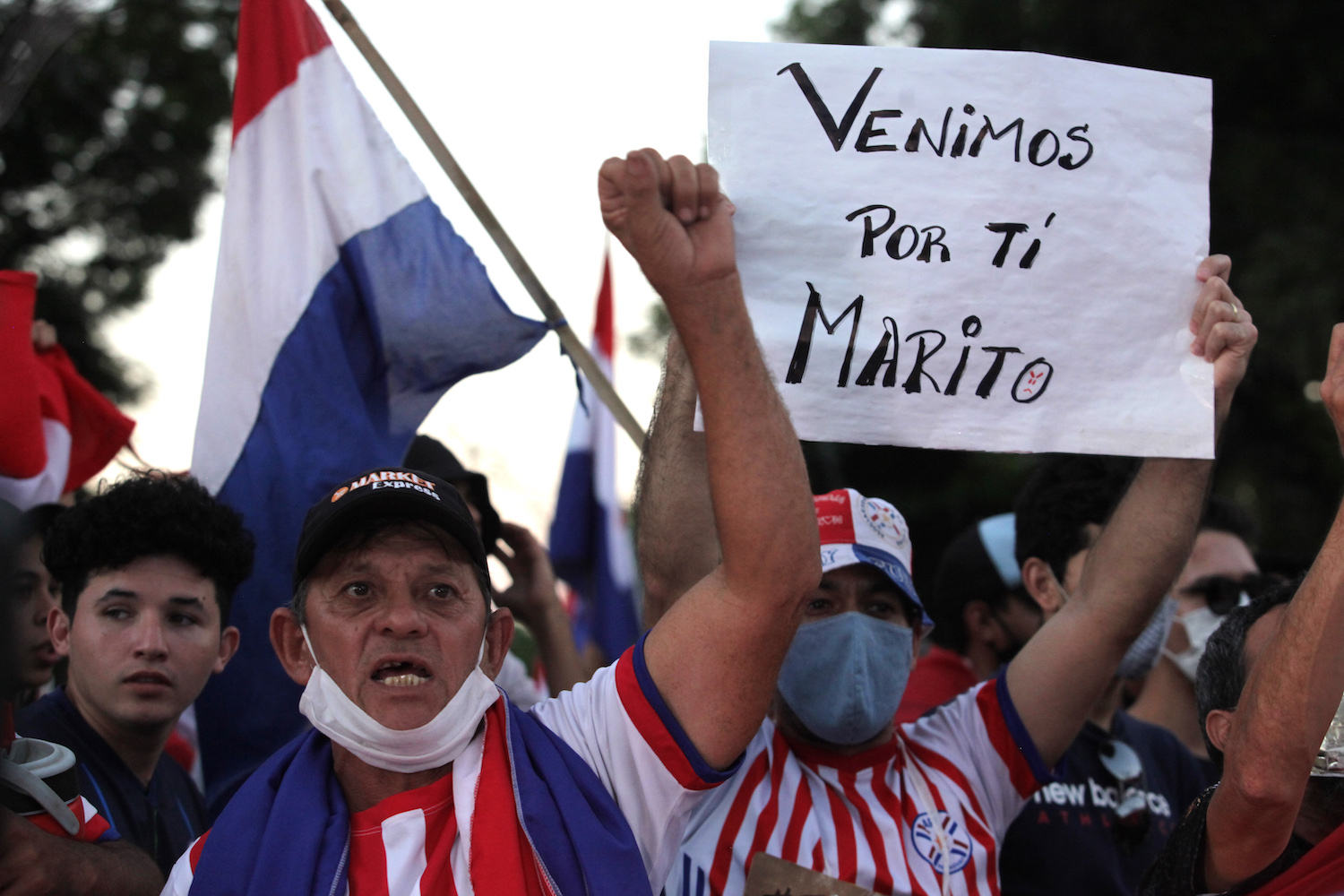 """A demonstrator holds a sign that reads """"We come for you, Marito"""" during a protest against President Mario Abdo Benitez's handling of the pandemic in Asuncion, Paraguay on March 7, 2021."""