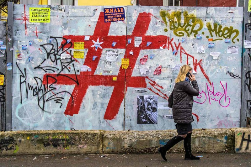 A woman speaks on a mobile phone as she walks past a graffiti-covered wall with a giant hashtag sign near Kursky railway station in Moscow on Nov. 17, 2017.