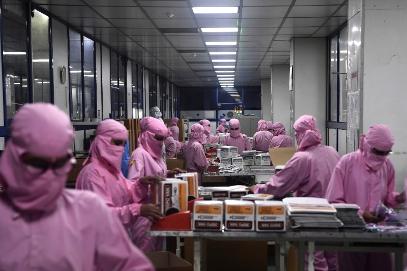 Workers pack syringes at the Hindustan Syringes and Medical Devices factory in Faridabad, India, on Sept. 2, 2020.