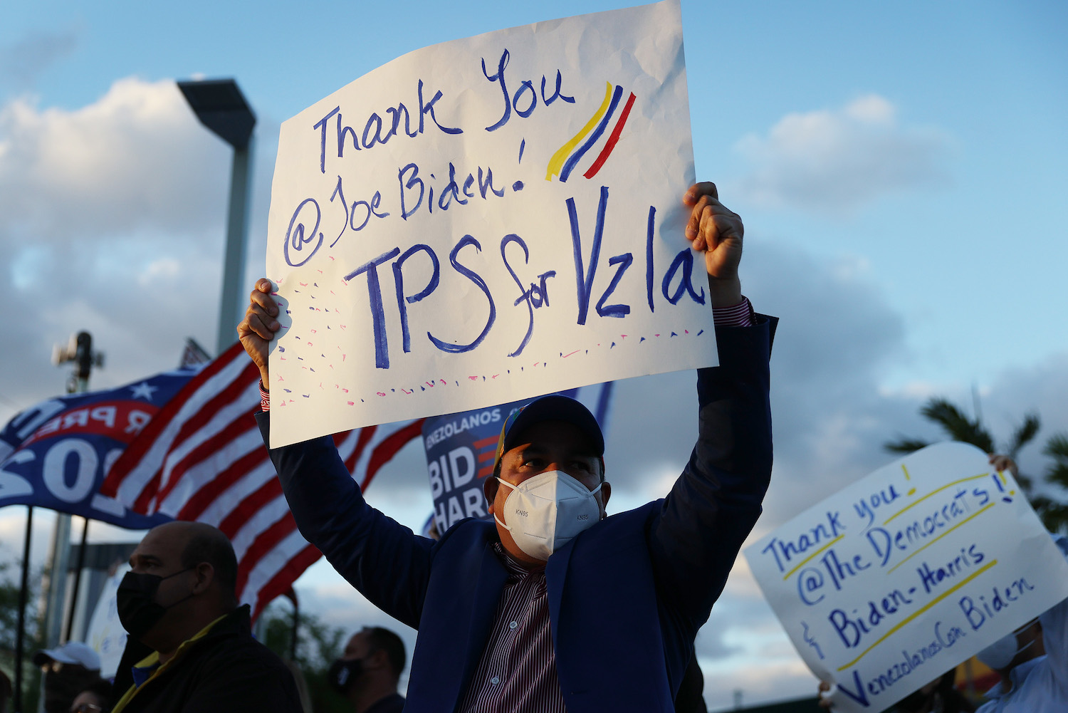 People with signs show their support for an order signed by U.S. President Joe Biden granting temporary protective status for thousands of Venezuelans in Doral, Florida on March 09.