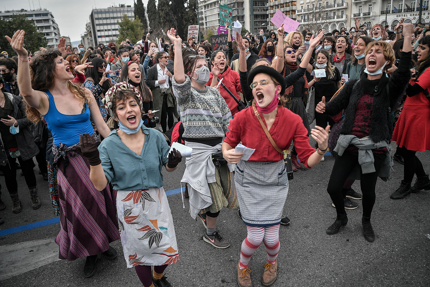Women chant a satirical song in front of the Greek parliament in Athens during a demonstration on International Women's Day, March 8. LOUISA GOULIAMAKI/AFP via Getty Images
