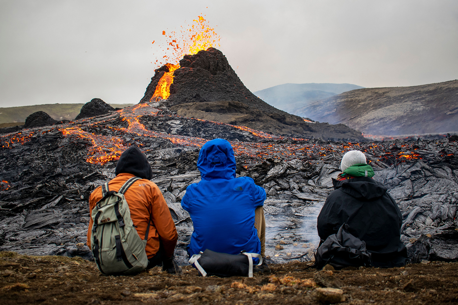 Hikers watch as lava flows from the Fagradalsfjall volcano about 25 miles west of Reykjavik, Iceland, on March 21. JEREMIE RICHARD/AFP via Getty Images