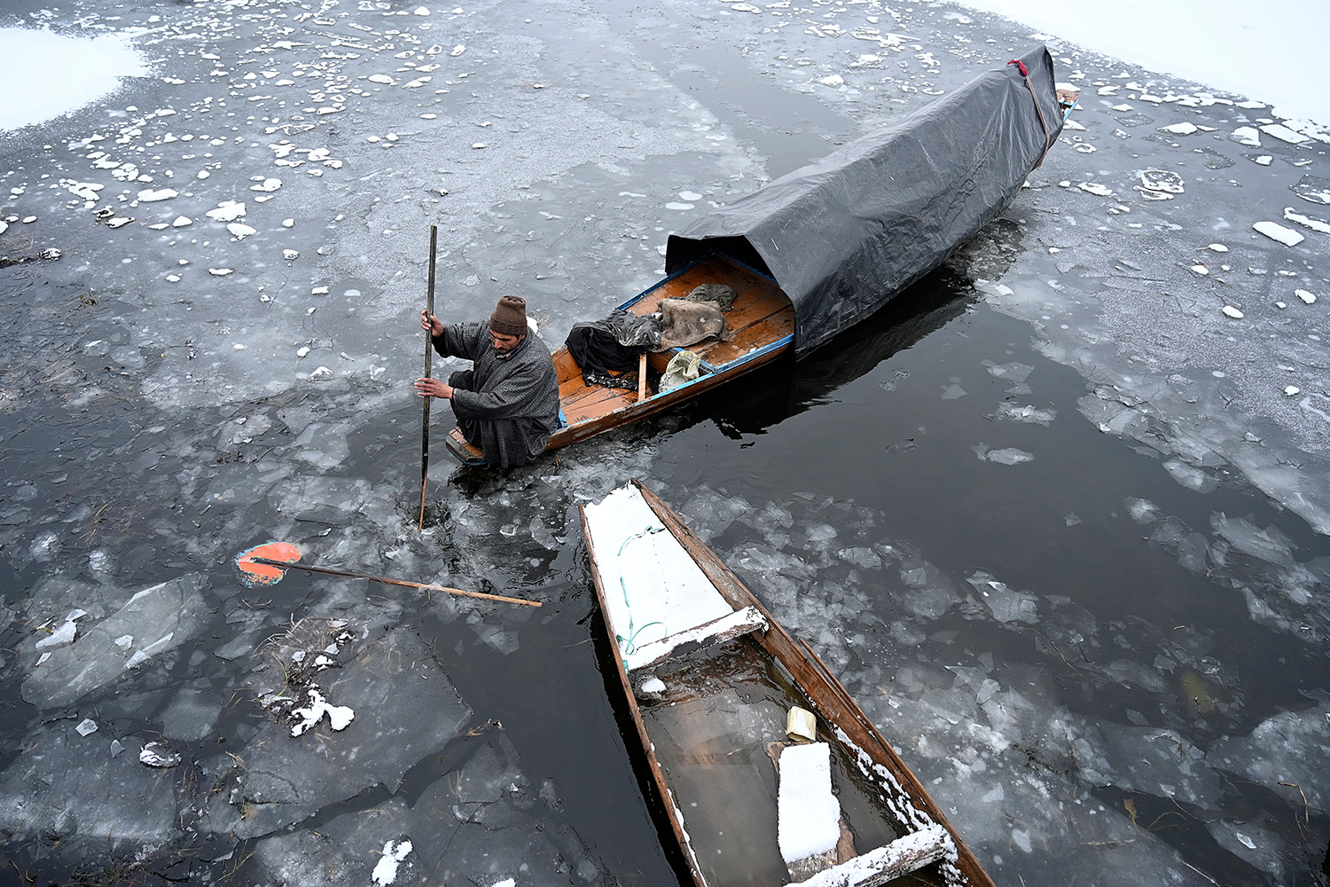A man rows a boat near a frozen portion of Dal Lake in Srinagar—in the territory of Jammu and Kashmir—on Feb. 1. TAUSEEF MUSTAFA/AFP via Getty Images