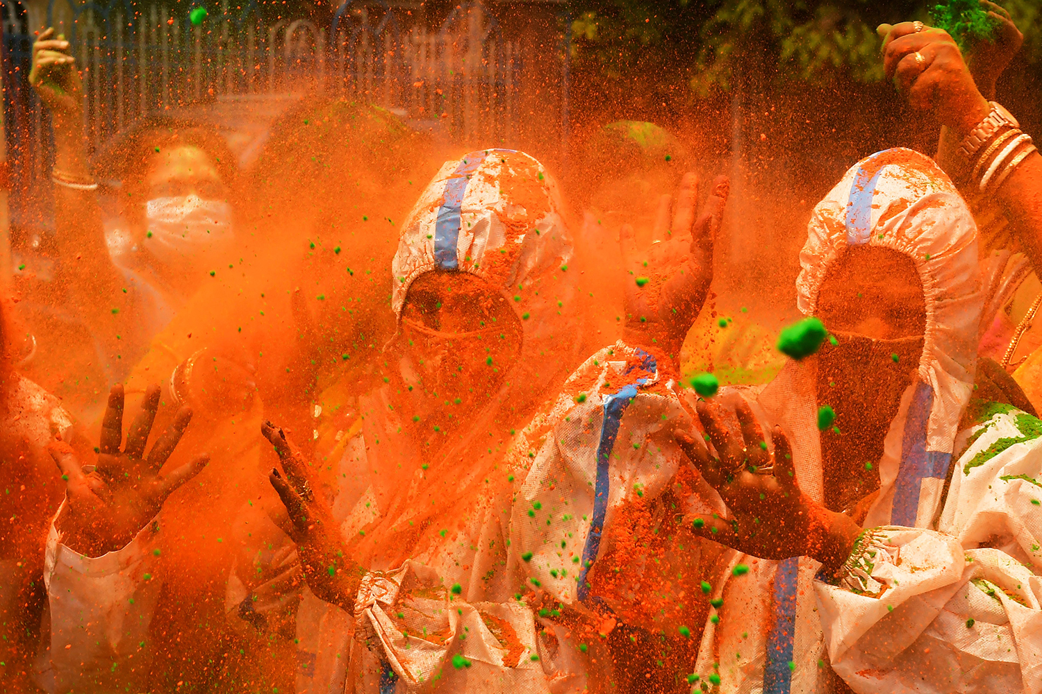 People wearing protective suits as a preventive measure against the spread of COVID-19, play with colored powders as they celebrate Holi, the spring festival of colors, in Kolkata, India, on March 29. DIBYANGSHU SARKAR/AFP via Getty Images