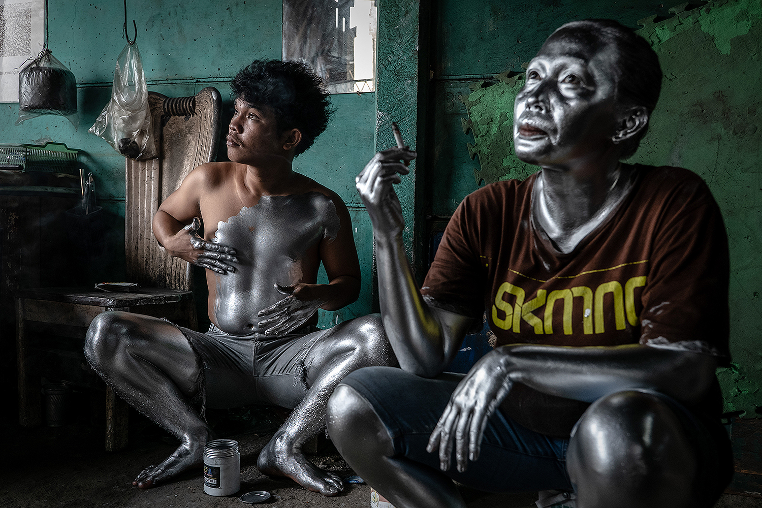 "Fernandes, left, applies silver paint to his body before heading out to earn money as a living statue, or ""Silver Man,"" in Depok, Indonesia, on March 10. Ulet Ifansasti/Getty Images"