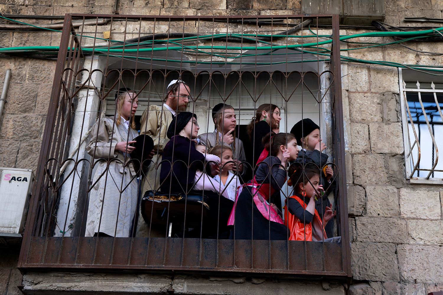 Orthodox Jews watch from their balcony in Jerusalem as people scuffle with Israeli police during Purim celebrations Feb. 28. MENAHEM KAHANA/AFP via Getty Images