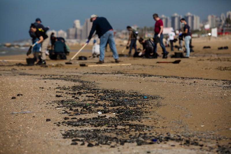 Israelis clean oil spill off Haifa's coast.