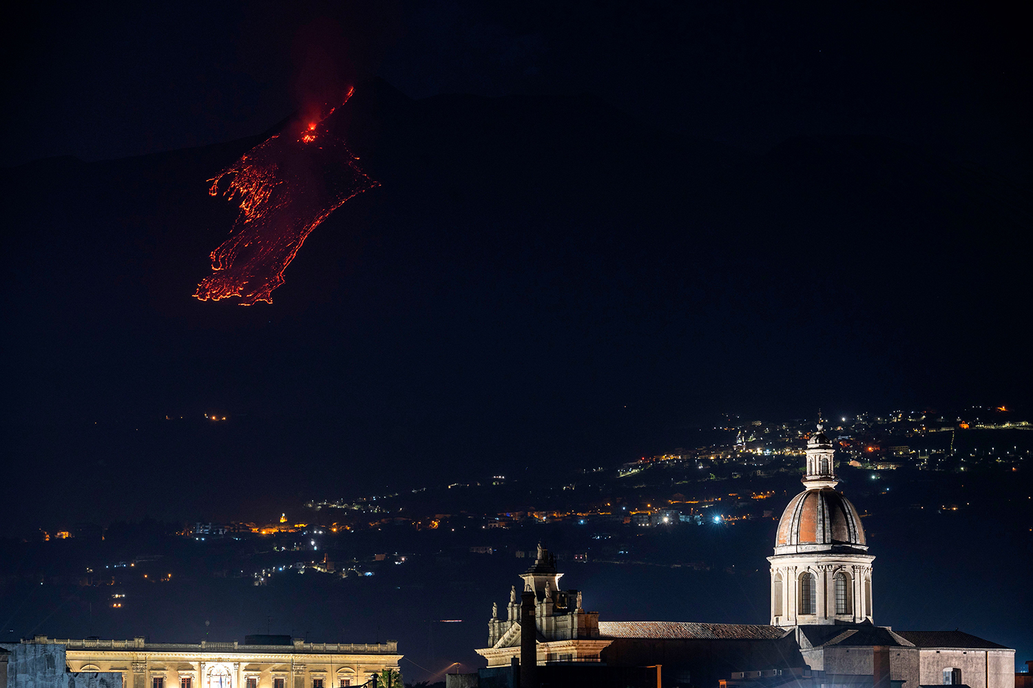 Lava flows along the sides of the southern crater of Italy's Mount Etna volcano, as seen in Porto di Riposto, Sicily, on Feb. 24. GIOVANNI ISOLINO/AFP via Getty Images