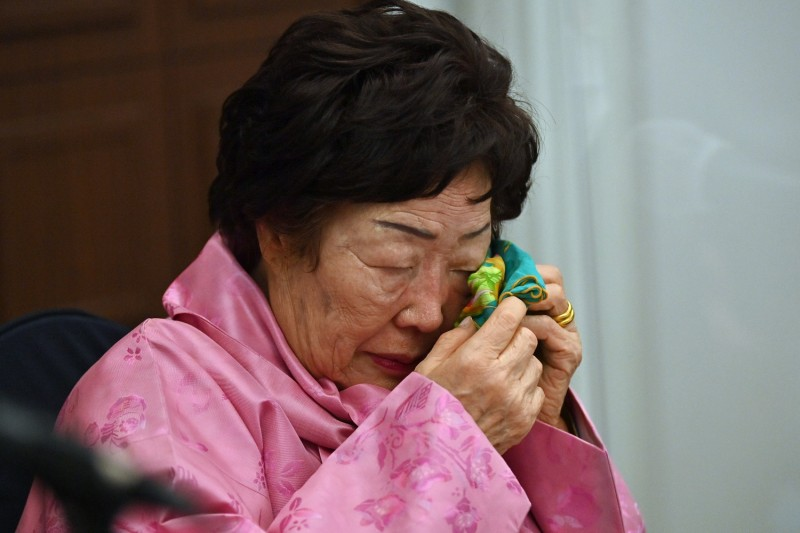 An elderly Korean woman weeps at a press conference.
