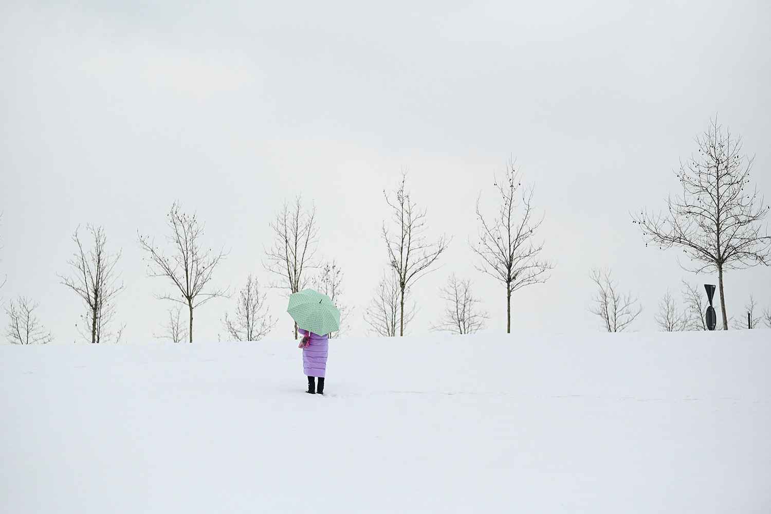 A woman walks along a snowy road near Pristina, Kosovo, on March 24 following a week of heavy snowfall. ARMEND NIMANI/AFP via Getty Images