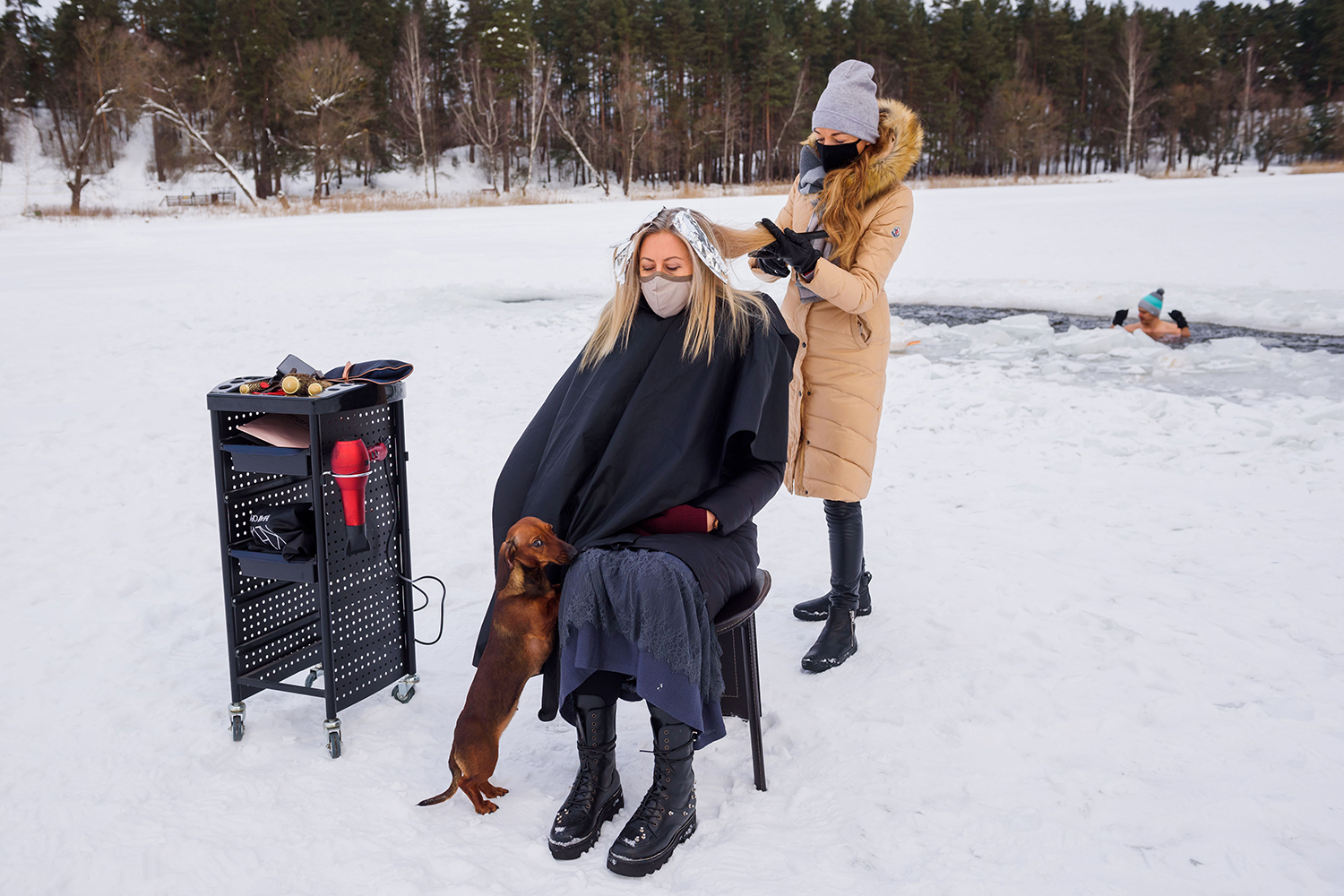 A hairdresser cuts a client's hair while a swimmer enjoys a dip in an ice hole on Lake Babelitis in Riga, Latvia, on Feb. 15. Hairdressers are not allowed to work indoors due to the pandemic. GINTS IVUSKANS/AFP via Getty Images