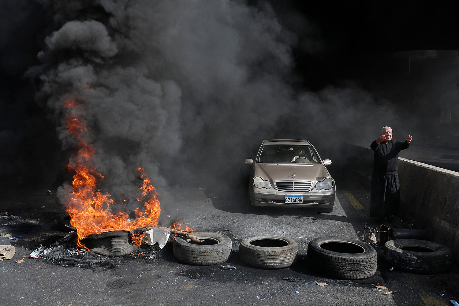 A Maronite Christian priest pleads with anti-government protesters to let his car pass as he stands next to burning tires at a makeshift roadblock in Zouk Mosbeh, Lebanon, on March 8. Protesters were demonstrating against the dire economic and social conditions. JOSEPH EID/AFP via Getty Images