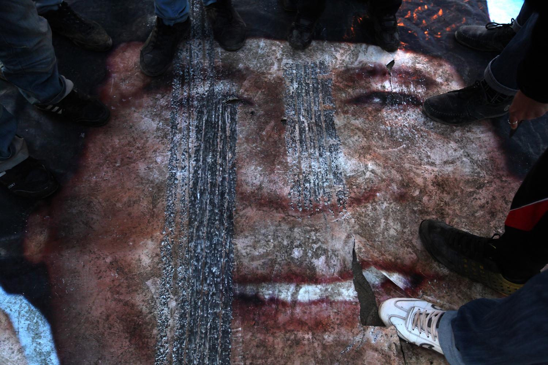 As world powers ramp up pressure on leader Muammar al-Qaddafi's regime, Libyan protesters step on a poster of Qaddafi in Benghazi, Libya, on Feb. 28, 2011.