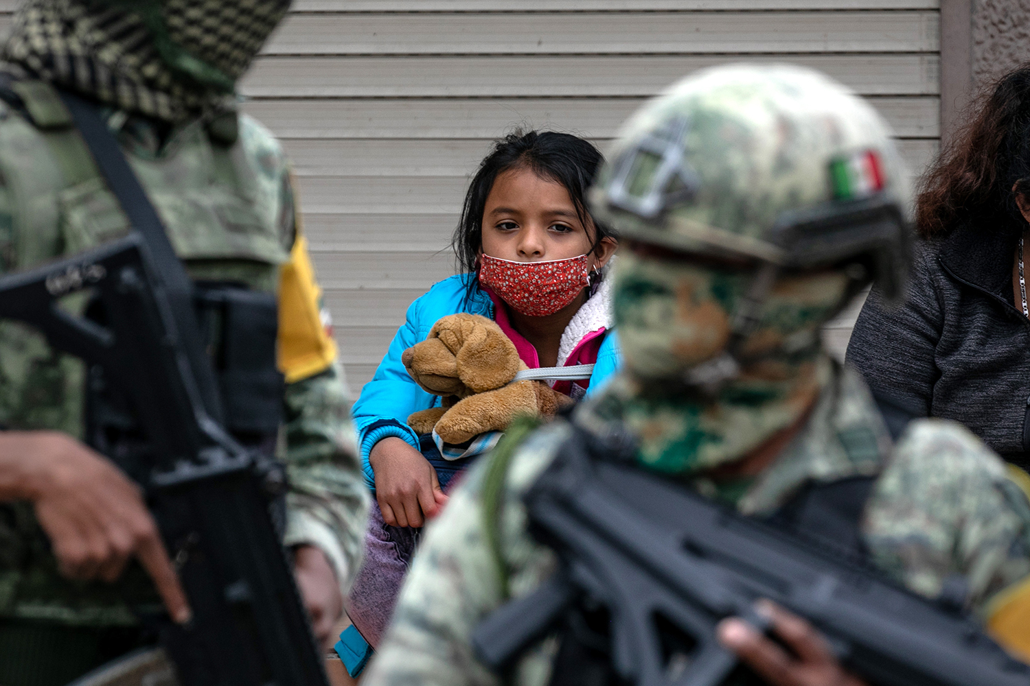 As Mexican military police stand guard, Central American immigrants wait at a camp for entry into the United States in Matamoros, Mexico, on Feb. 22. Immigration authorities have begun to allow some asylum seekers with active cases into the United States. John Moore/Getty Images