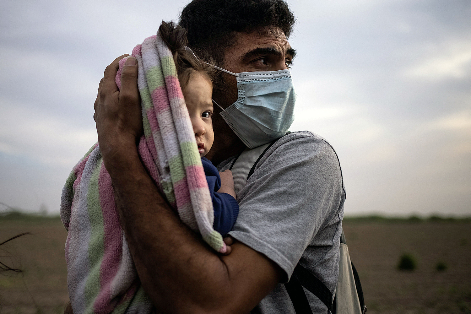 Francisco, 34, an asylum-seeking migrant from Honduras, cradles his 9-month-old daughter, Megan, from the early morning cold and wind in La Joya, Texas, as they await transportation to a processing center after crossing the Rio Grande into the United States from Mexico on a raft March 25. Adrees Latif/REUTERS