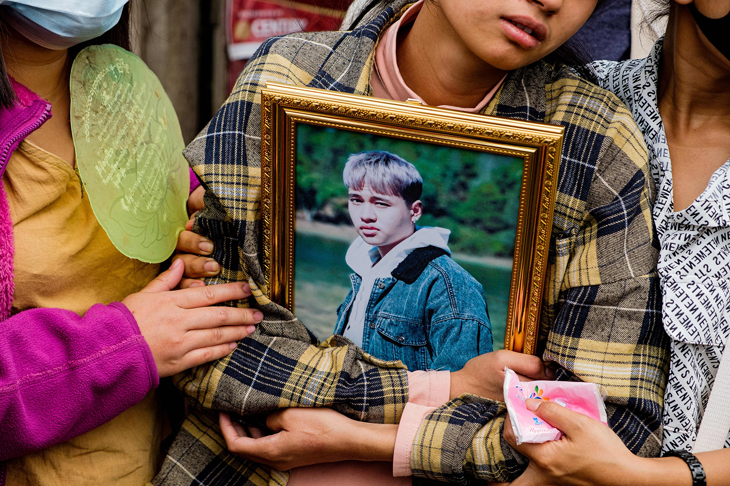 A relative holds the portrait of a protester who died amid a crackdown on demonstrations against Myanmar's military coup during his funeral in Taunggyi, Shan state, on March 29. STR/AFP via Getty Images
