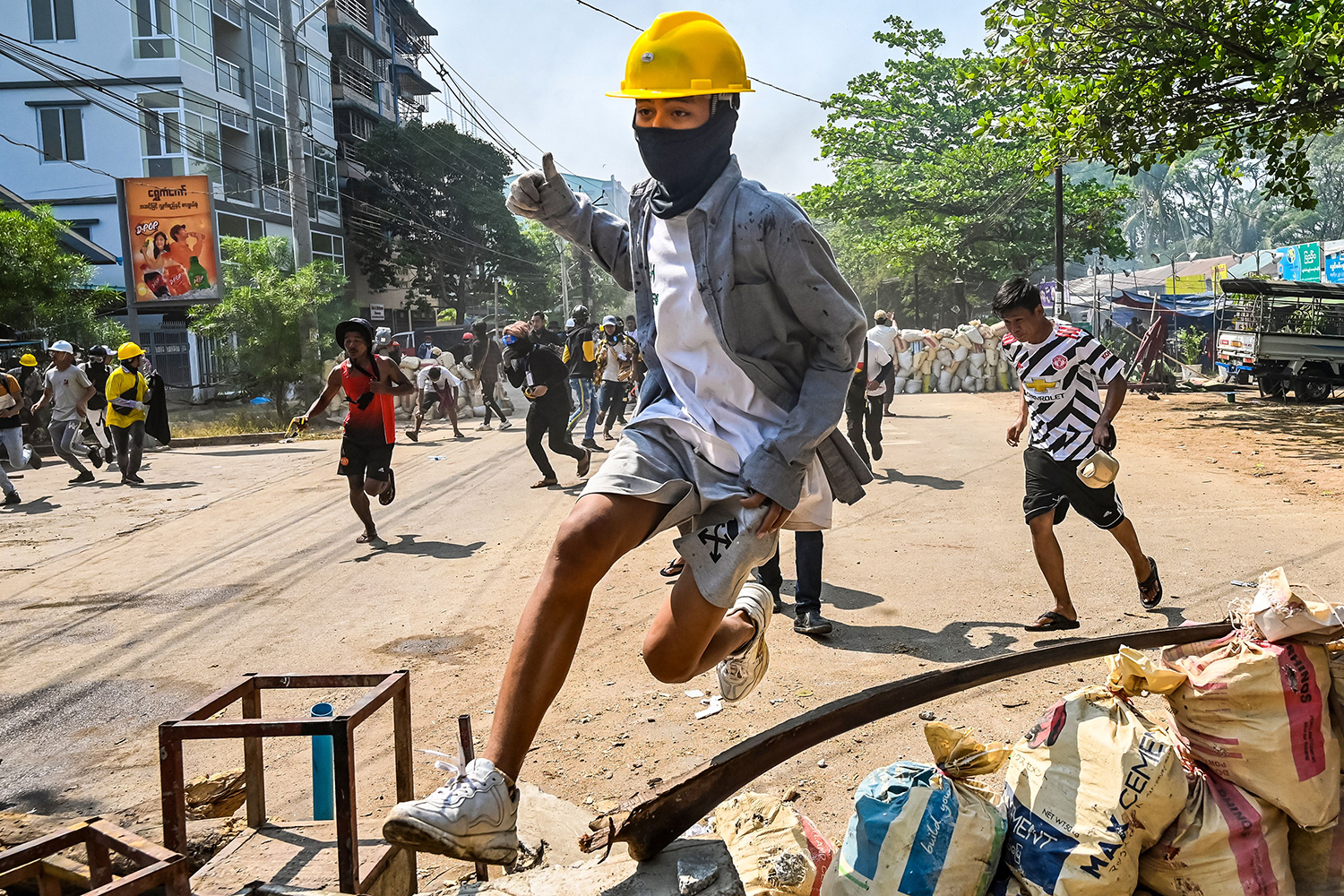 A protester jumps over a makeshift barricade during a crackdown by security forces on a demonstration against the military coup in Yangon, Myanmar's Thaketa Township on March 19. STR/AFP via Getty Images