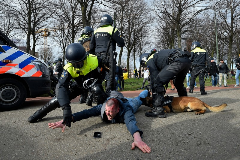 Dutch anti-riot police officers detain a man during a demonstration against the government and COVID-19 measures in The Hague, Netherlands, on March 14. JOHN THYS/AFP via Getty Images