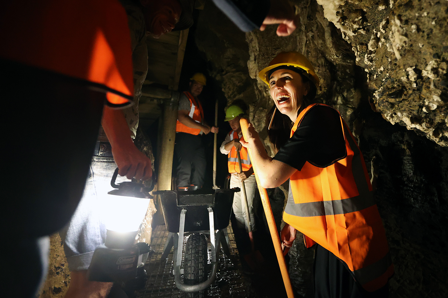 Prime Minister Jacinda Ardern helps shovel metal to reduce flooding as she visits Kawiti Caves in Waitangi, New Zealand, on Feb. 3. Fiona Goodall/Getty Images