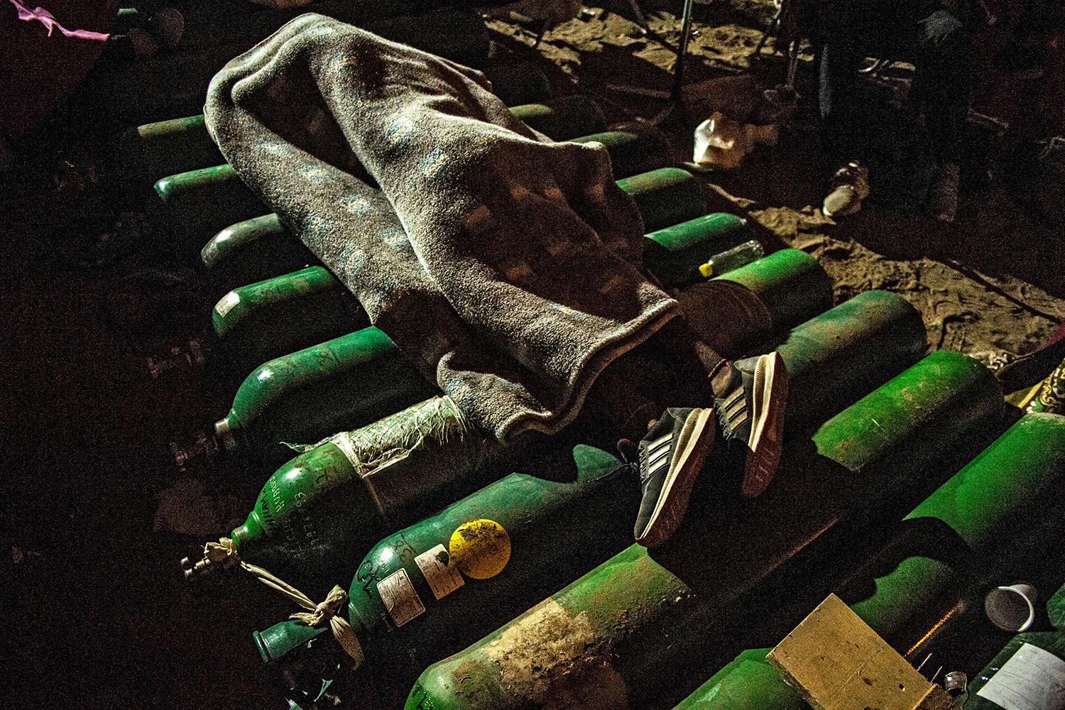 A person sleeps on empty oxygen cylinders while waiting to get them refilled in Villa El Salvador, on the southern outskirts of Lima, Peru, on Feb. 25. Relatives of COVID-19 patients are desperate for oxygen to keep their loved ones alive during a fierce second wave of the pandemic in Peru. ERNESTO BENAVIDES/AFP via Getty Images