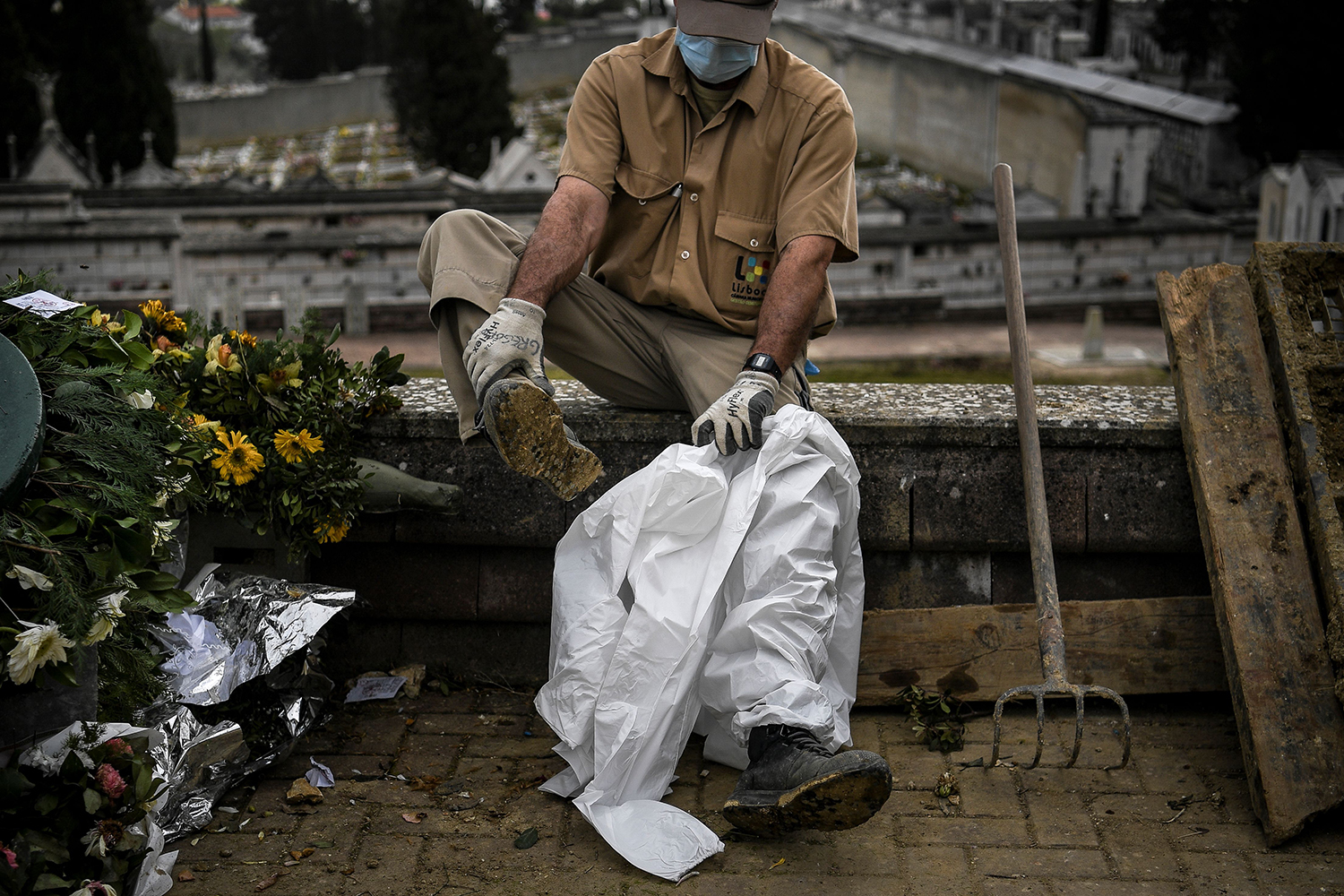 A grave digger puts on his protective suit before the burial of a COVID-19 victim at the Alto de Sao Joao cemetery in Lisbon, Portugal, on Feb. 18. PATRICIA DE MELO MOREIRA/AFP via Getty Images